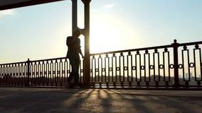 在桥梁的年轻人电话,跃迁高愉快地在精采日落在Slo Mo 股票录像
