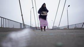 在桥梁的年长无家可归的妇女逗留在冷的有风灰色天气的内河港附近请求帮助和乞求 股票录像