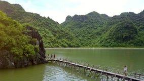 在桥梁的游人步行接近海洋海湾的岩质岛 股票视频