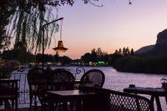 在桥梁的舒适的咖啡馆在日落的河 免版税库存照片