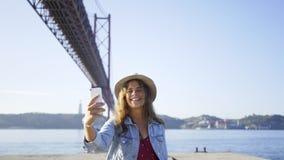 在桥梁附近的微笑的女性采取的selfie 影视素材