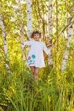 在桦树中的小女孩 免版税库存照片