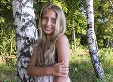 在桦树中的微笑的女孩在日出 图库摄影