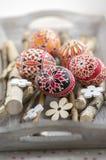 在桦树分支的自创手工制造被绘的复活节彩蛋在灰色木盘子,传统hnadcraft鸡蛋,白花 免版税库存图片