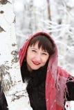 在桦树森林附近的微笑的女孩在冬天 免版税库存照片