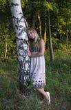 在桦树附近的女孩在一件美丽的礼服 库存照片