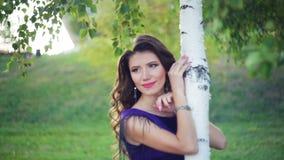 在桦树附近的年轻美丽的妇女在夏天绿色公园 股票录像