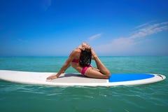 在桨水橇板一口的女孩体操 库存图片