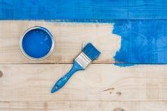 在桶有蓝色油漆的和刷子上的平的位置在木板 免版税库存照片