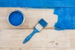 在桶有蓝色油漆的和刷子上的平的位置在木板 图库摄影
