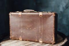 在桶的上面的老棕色手提箱 库存照片