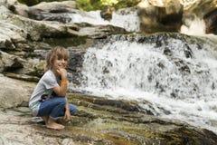 在桶的瀑布的旁边女孩在丛林地带de Irati的 免版税库存图片