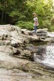 在桶的瀑布的旁边女孩在丛林地带de Irati的 库存图片