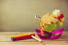 在桶的Hamantaschen曲奇饼有grogger的吵闹制造商和狂欢节面具 purim节日的礼物 免版税库存照片