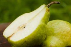 在梨的背景绿色一半 免版税库存照片