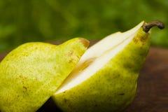 在梨的背景绿色一半 免版税库存图片