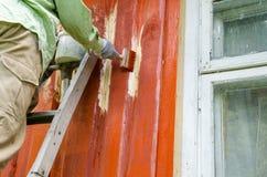 在梯子油漆木房子墙壁上的画家人 免版税库存图片