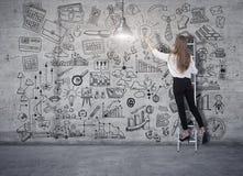 在梯子的年轻女人身分和画在一个混凝土墙上的一个经营计划剪影 3d回报在拼贴画的元素 免版税库存图片