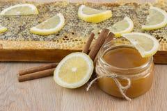在梳子的金黄蜂蜜在瓶子和黄色柠檬 库存照片