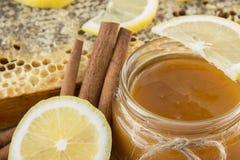 在梳子的金黄蜂蜜在瓶子和黄色柠檬 免版税库存照片
