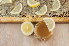 在梳子的金黄蜂蜜在瓶子和黄色柠檬 库存图片