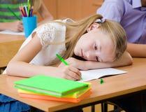 在检查期间,疲乏的女小学生损坏眼力 图库摄影