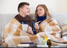 在检查热病的毯子下的病态的夫妇 免版税库存图片