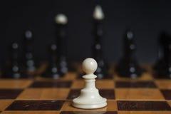在棋枰的棋子白色典当 一盘象棋 反对所有的典当 库存图片
