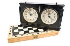 在棋枰的老棋时钟 免版税库存图片
