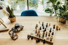 在棋盘、葡萄酒照相机和绿色植物的国际象棋棋局 库存图片