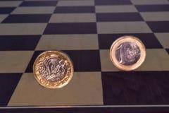 在棋盘的磅和欧元硬币 免版税库存照片