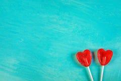 在棍子的两个红色心脏形状糖果棒棒糖在绿松石背景角落位置 华伦泰浪漫爱贺卡 免版税库存照片