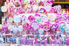 在棍子的五颜六色的棒棒糖待售在商店窗口里 库存照片