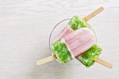 在棍子的多彩多姿的桃红色绿的冰淇凌 白色背景,顶视图,拷贝空间 图库摄影
