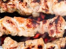 在棍子的猪肉在格栅被烤 免版税库存图片
