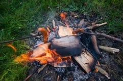 在棍子的香肠,在露营地的壁炉 免版税库存图片