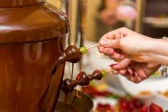 在棍子自助餐承办酒席的巧克力葡萄 库存照片