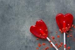 在棍子花的两个红色心脏形状糖果棒棒糖在黑暗的石背景 华伦泰浪漫爱贺卡 库存图片