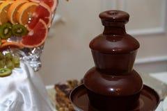 在棒棒糖的可口巧克力喷泉涮制菜肴在豪华wedd 免版税图库摄影