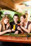 在棒的青年人饮用的鸡尾酒 库存照片