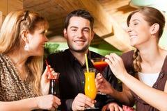 在棒的青年人饮用的鸡尾酒 免版税库存照片