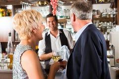 在棒的高级夫妇与杯酒在手中 免版税图库摄影