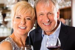 在棒的高级夫妇与杯酒在手中 免版税库存图片