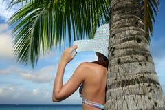 在棕榈树下观看海洋梦想的妇女 免版税库存图片