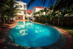在棕榈树中的美丽的大卵形水池 免版税图库摄影
