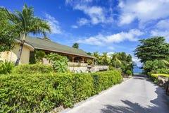 在棕榈树之间的旅馆在热带海岛, la digue, seychelle上 免版税库存照片