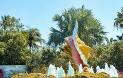 在棕榈树和叶子前面的巨型贝壳喷泉 库存图片