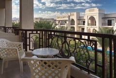 在棕榈树的看法和从一个大阳台的一旅馆foreside与椅子和桌 与蓝天和白色云彩的晴天 免版税图库摄影