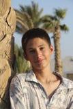 在棕榈附近的微笑的少年男孩 免版税库存照片