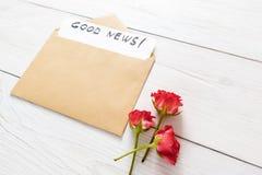 在棕色信封的好消息笔记与花 免版税图库摄影